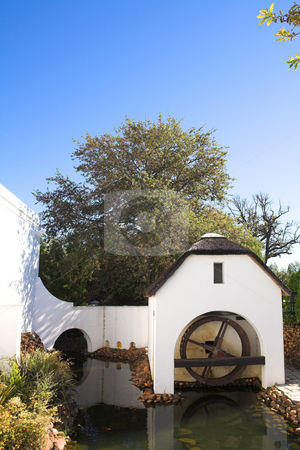 Old refurbished waterwheel and watermill stock photo, Old watermill next to winery on Plaisir de Merle, South Africa, on a sunny summers day by Sean Nel
