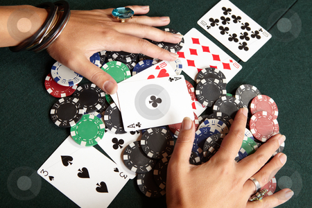 Card gambling stock photo, Winning hand, three of a kind, Aces high. Playing cards, chips and player pulling winnings to herself on a green felt poker table by Sean Nel