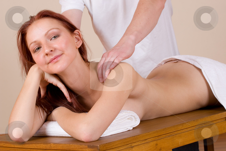 Massage #32 stock photo, Woman lying on massage table with the hands of male masseuse on her back and shoulders - Looking at camera by Sean Nel
