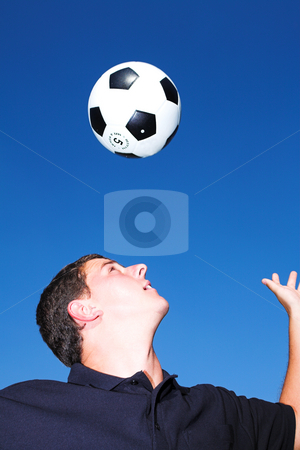 Football player with a soccer ball  stock photo, A male soccer (football) player, referee or coach catching a soccer ball and outlined against a blue sky. There is movement on his hands and the ball but elements of the face is sharp. by Sean Nel