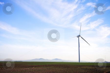 Eco friendly windpower stock photo, Wind powered electricity generator standing against the blue sky in a green field on the wind farm. A man is walking past the first generator by Sean Nel