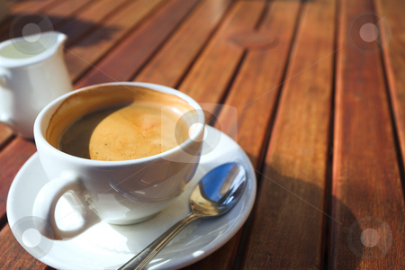 Early morning coffee stock photo, A cup of coffee on a wooden table in an outdoor cafe. Shallow depth of field, focus on the rim of the cup by Sean Nel