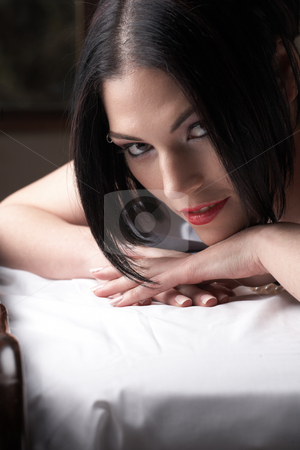 Nude adult woman stock photo, Sensual naked young black haired adult Caucasian woman, lying on a bed high key image. by Sean Nel