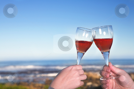 Wineglasses toasted next to the sea stock photo, Couple toasting wineglasses next to the ocean against a blue sky on a summers day by Sean Nel