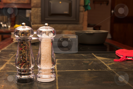 Salt and pepper shaker stock photo, Salt and pepper shaker on a work surface inside a kitchen with a stove and oven in the background by Sean Nel