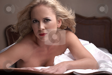 Nude adult woman stock photo, Sensual naked young blonde adult Caucasian woman, wrapped in a satin, silk sheet on a bed in her bedroom. High contrast lighting. by Sean Nel