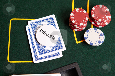 Card gambling stock photo, Playing cards, chips and a dealer chip on folded cards by Sean Nel