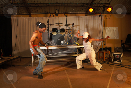 Two freestyle hip-hop dancers stock photo, Two freestyle hip-hop dancers a man and a woman at a training session on stage with instruments in the background by Sean Nel