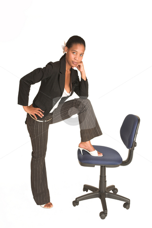 Mida Matsimela #26 stock photo, African business woman dressed in black jacket.  Standing with one foot on an office chair. by Sean Nel