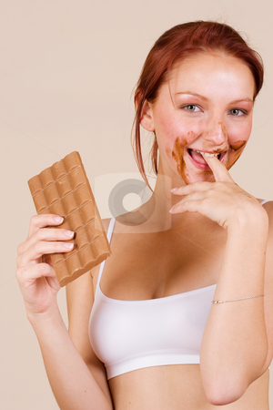Chocolate #1 stock photo, Redheaded girl eating chocolate, biting finger by Sean Nel