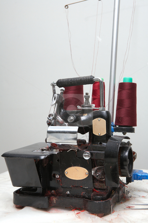 Industrial overlock machine stock photo, Old industrial overlocking machine in sewing factory with red thread by Sean Nel