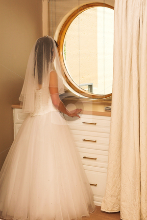 Wedding #42 stock photo, Bride standing in front of a mirror in a room by Sean Nel