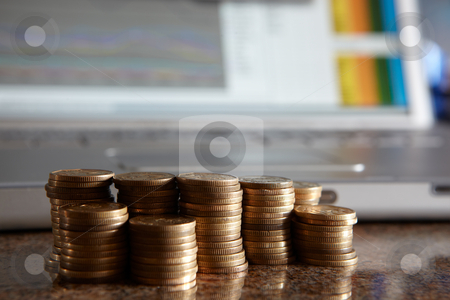 Counting money stock photo, Stacks of coins on a marble table with a notebook computer blurred in the background running financial data, shallow depth of field by Sean Nel