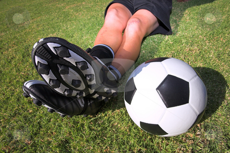 Football player with a soccerball on soccer pitch stock photo, A male soccer (football) player, referee or coach sitting with crossed legs. Focus on ball and togs by Sean Nel