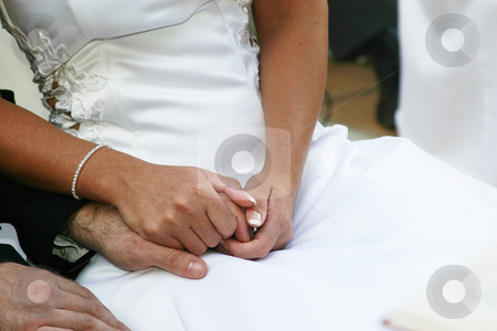 Holding hands stock photo, Bride and groom holding hands at wedding ceremony by Sean Nel