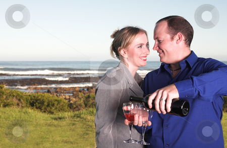 Couple next to the coast drinking wine stock photo, Loving young adult couple drinking wine outside next to the coast. Man is pouring wine for the woman. Husband and wife after work by Sean Nel