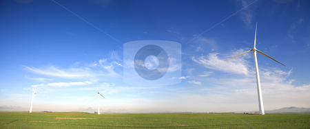 Wind powered turbine stock photo, Panoramic image of wind powered electricity generator standing against the blue sky on a wind farm by Sean Nel