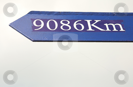 Distance sign  stock photo, Blue distance and direction marker against a cloudy sky by Sean Nel
