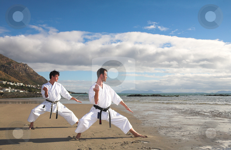 Men practicing Karate on the beach stock photo, Young adult men with black belt practicing a Kata on the beach on a sunny day by Sean Nel