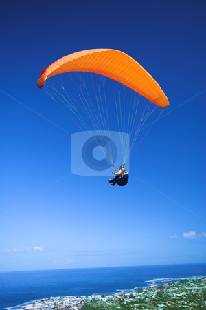 Paraglider launching from the mountain ridge stock photo, Paraglider launching from the ridge with an orange canopy and the sun from behind. The paraglider is standing out against the blue sky and the shot is taken right after takeoff. The paraglider and pilot is both sharp by Sean Nel