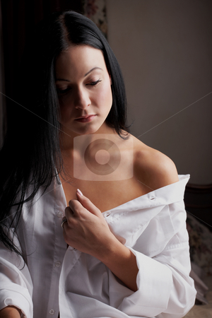 Intimate young lovers stock photo, Young adult Caucasian woman in a white mens shirt, busy undressing as a part of sexual foreplay by Sean Nel