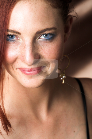 Female Fashion Model stock photo, Young female adult fashion model with natural red hair and freckles in black chiffon evening wear with silver bracelet (Copper silk background)  by Sean Nel