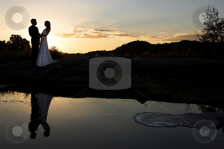 Sunset bride stock photo, Bride and groom next to river at sunset by Sean Nel