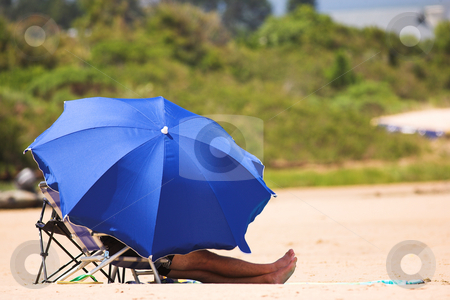 Beach #2 stock photo, Man relaxing on the beach under a blue umbrella by Sean Nel