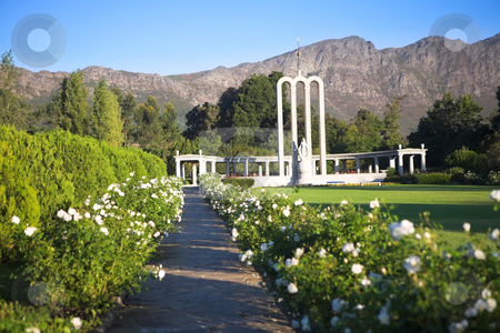 The Huguenot Monument stock photo, Pathway with white flowers leading to the Huguenot Monument in summer with green grass and blooming gardens in Franschhoek, Western Cape, South Africa. Shallow DOF, Focus on Landmark by Sean Nel