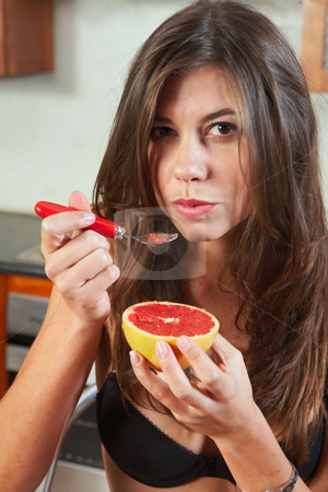 Sexy brunette eating breakfast stock photo, Sexy young adult brunette woman in black lingerie eating a grapefruit for breakfast in her kitchen by Sean Nel