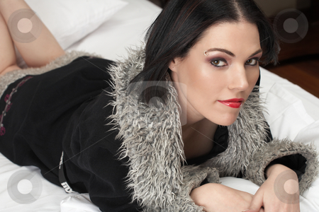 Nude adult woman stock photo, Sensual naked young Black haired adult Caucasian woman, wrapped in a black fur lined coat on a bed in her bedroom. High contrast lighting. by Sean Nel