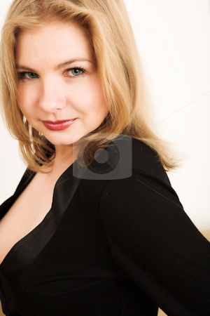 Beautiful blonde adult woman stock photo, Portrait of a beautiful blonde Russian woman with blue eyes, looking over her shoulder against a white wall (not an isolation) by Sean Nel