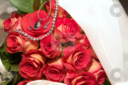 Wedding bouquet stock photo, Red rose wedding bouquet with a diamond pendant necklace and other jewelry draped in a white veil. by Sean Nel