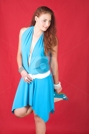 Female fashion model stock photo, Young female adult fashion model with natural red hair and freckles in a blue summers dress with white belt (red textured faux leather background) by Sean Nel