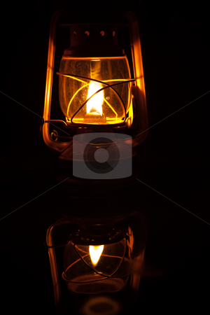 Storm Lantern stock photo, Yellow storm lantern burning at night on a wet table by Sean Nel