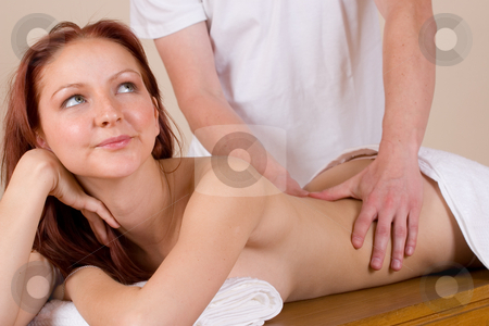 Massage #33 stock photo, Woman lying on massage table with the hands of male masseuse on her back and shoulders - Eyes looking up by Sean Nel