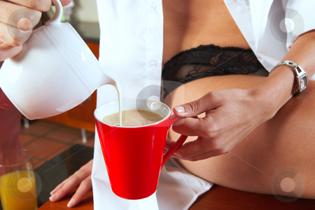 Sexy brunette eating breakfast stock photo, Sexy young adult brunette woman in black lingerie pouring milk in her breakfast coffee in her kitchen by Sean Nel