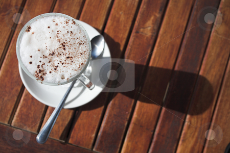 Cafe latte from above stock photo, A cup of cafe latte on a wooden table in an outdoor cafe. Shallow depth of field, focus on the foam and chocolate sprinkling. by Sean Nel