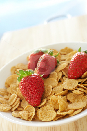 Breakfast cereal with strawberries stock photo, Fresh red strawberries on breakfast cereal in a white bowl on a kitchen table by Sean Nel