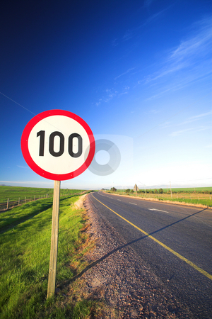 Road sign for speed limit stock photo, Warning sign or road sign for the maximum speed limit next to an empty road on a sunny summer day. Focus on the numbers  by Sean Nel