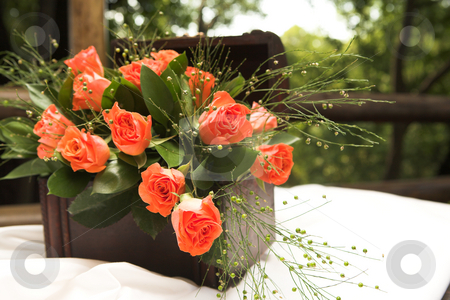 Rose flower arrangement stock photo, A flower arrangement with red roses and green leaves inside a small wooden treasure chest on a table at a wedding reception by Sean Nel