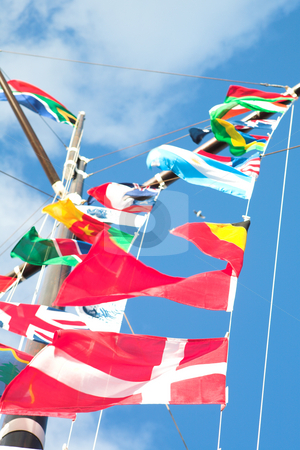 Flags of the world stock photo, Various flags of various countries displayed together on a signal mast of a ship (focus on the red flags at the bottom) by Sean Nel