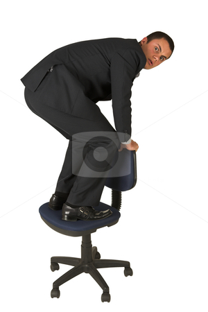 Businessman #298 stock photo, Businessman wearing a suit and a grey shirt.  Standing  on an office chair. by Sean Nel