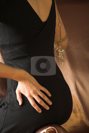 Italian adult woman stock photo, The back of a beautiful young sexy adult Italian woman in formal black dress on a textured wooden background, sitting on a luxurious couch ? Hard light, high key by Sean Nel