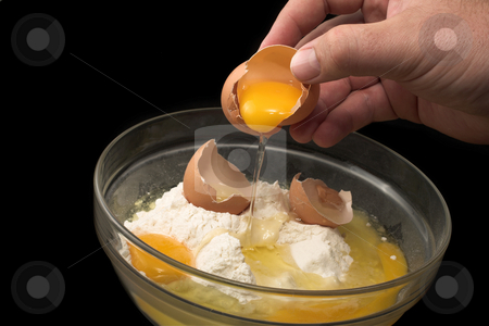 Baking #8 stock photo, Hand breaking an egg into a glass bowl with flour, black background by Sean Nel