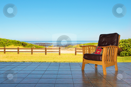 Comfortable chair on patio at seaside stock photo, A comfortable leather chair on a patio at a seaside residence or holiday home by Sean Nel