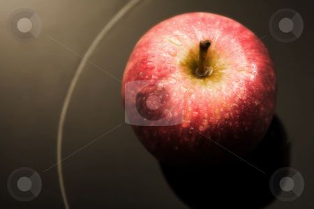 Fresh red apple stock photo, Fresh red apple with drops of water on a black glass backdrop - defocussed (digital artwork) by Sean Nel