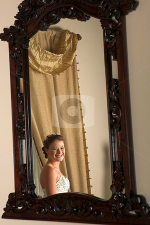 Beautiful caucasian woman stock photo, Beautiful caucasian woman with brown hair wearing luxurious silk wedding dress looking in the mirror by Sean Nel