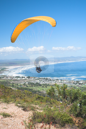 Paraglider ridge soaring next to the mountain stock photo, Paraglider launching from the ridge with an orange canopy and the sun from behind. The paraglider is standing out against the blue sky and the shot is taken right after takeoff. The paraglider and pilot is both sharp by Sean Nel