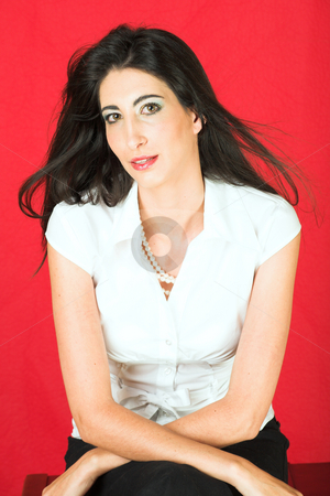 Beautiful young Italian woman stock photo, Beautiful young adult Italian businesswoman with long black hair, pearls and a white blouse on a textured red faux leather background by Sean Nel